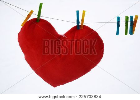 Red Heart Hanging At Clothesline On White Background. Big Red Heart On Snow Background. Valentines D