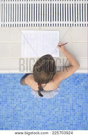 Child Girl Doing Holidays Homework Over Swimming Poolside. Summer Homework Concept For Children