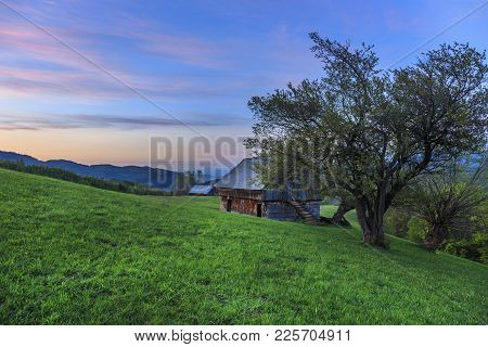 Rural Farm With Old Wooden Hut At Sunset Near Bran, Transylvania, Romania