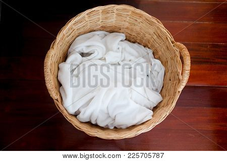 White Towels Waiting For Laundry In Wicker Basket