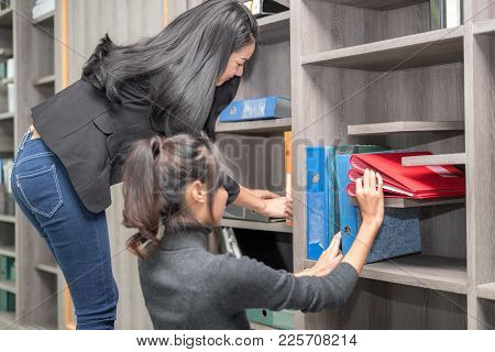 Secretary And Purchasing Manager Helping To Sort Out Company Files And Filing Account File In A Mode