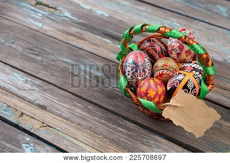 Pisanky In A Wicker Basket On A Wooden Background. Easter Eggs On A Wooden Table. A Busket With Holi