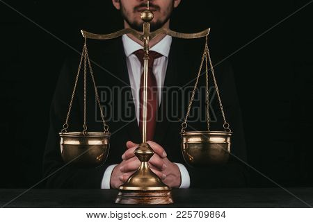 Cropped Shot Of Lawyer Sitting Behind Justice Scales Isolated On Black