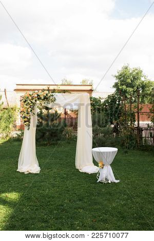 Open Air Decorated Area For The Wedding Ceremony With A Wooden Arch Decorated With Fresh Flowers And