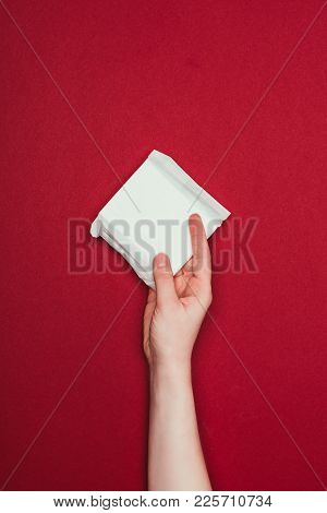 Partial View Of Woman Holding Menstrual Pad In Hand Isolated On Red