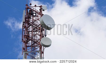 Cell Phone Tower Against A Blue Sky. Tower Of Communications With A Lot Of Different Antennas Under