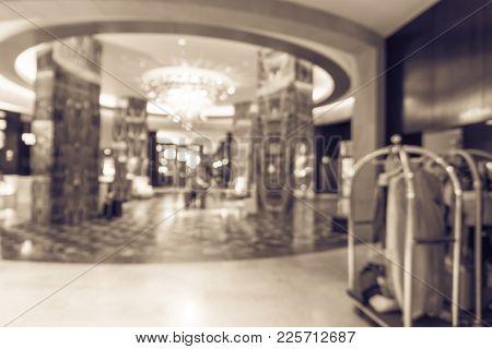 Blurred Luxury Lobby Reception Desk With Luggage Cart