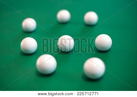 Eight Golf Balls Lying Against Green Background