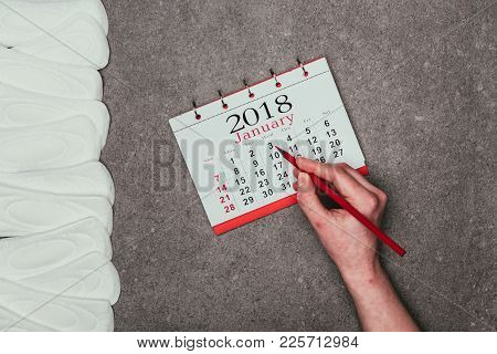 Cropped Shot Of Woman Pointing At Date In Calendar With Menstrual Pads Around On Grey Surface
