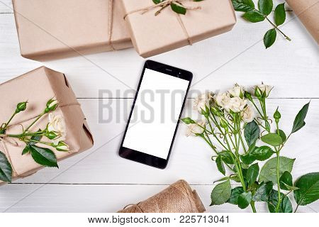 Closeup Of Mobile Smartphone With Blank Screen, Gift Boxes And Fresh Roses On Wooden Background, Cop