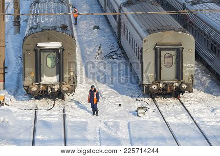 Moscow, Feb. 01, 2018: Winter Day View On Railway Maintenance Worker In Orange High-visibility Vest
