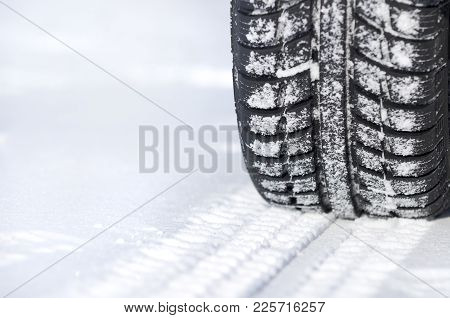 Car Tire In Winter On The Road Covered With Snow Close Up