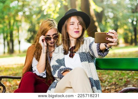 Girlfriends Taking A Selfie On A Bench In The Park