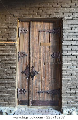 Ancient Wooden Door In A Brick Wall With A Forged Hinges And Lock