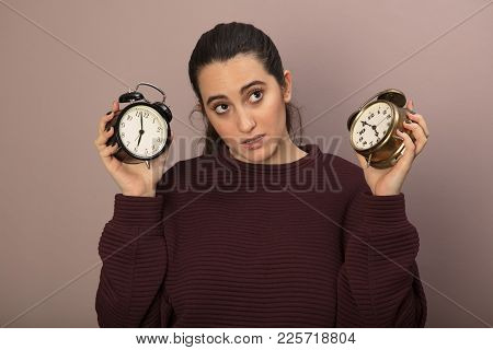 Thoughtful Woman Holding Up Two Old Fashioned Alarm Clocks With Bells Showing Different Times As She