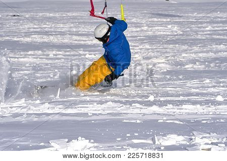 A Male Athlete Engaged In Snow Kiting On The Ice Of A Large Snowy Lake. He Goes Skiing In The Snow.