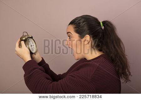 Horrified Woman Looking At The Time On An Old Fashioned Alarm Clock With Her Mouth Wide Open In Shoc