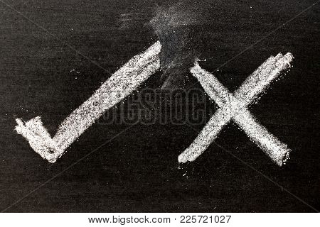 White Color Chalk Hand Drawing As Check Mark Of Right And Wrong Shape On Black Board Background