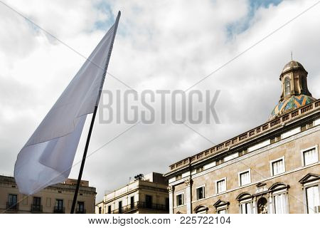 White Flag Waving In Front Of A Public Building In A European City