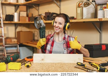 Young Woman In Plaid Shirt Gray T-shirt Noise Insulated Headphones Yellow Gloves Working In Carpentr