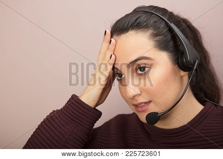 Close-up Portrait Of A Desperate Young Woman Listening To A Single Headphone With Microphone During