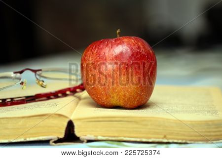 lovely ripe delicious apple and pages of an old book