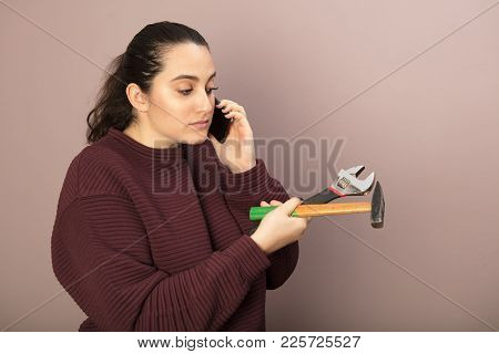 Young Woman Seeking Advice On Her Mobile Phone As She Holds A Spanner And Hammer In Her Hands In A D
