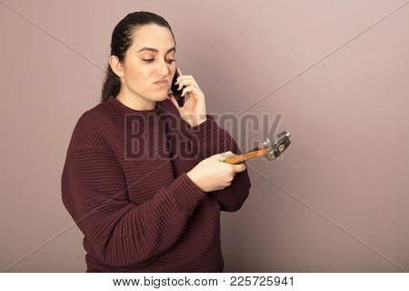 Helpless Woman Holding Hammer With Monkey Wrench While Talking On Phone Hands In A Diy Concept