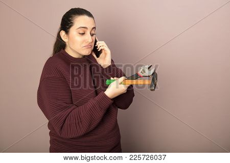 Helpless Woman Holding Hammer With Wrench Talking On Phone Hands In A Diy Concept