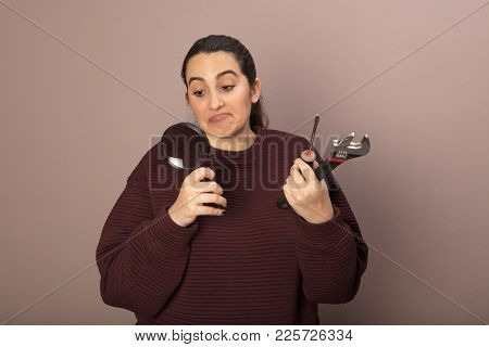 Hopeless Diy Ethusiast Woman As She Holds A Spanner, A Hammer And Manifying Glass In Her Hands