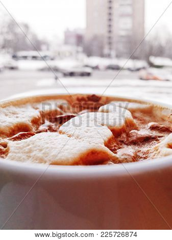 Cup Of Hot Cappuccino Coffee, Urban Background. Tasty Beverage In Front Of Window. Winter Street Wit