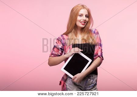 Young Woman Holfing A Digital Pc In Hands On Pink Background In Studio
