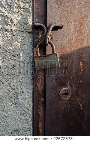 Old rusty door and rusty padlock. Basement door. Rusty padlock. Padlock. Rusty door. Door. Metal door. Grunge door. Grunge style.