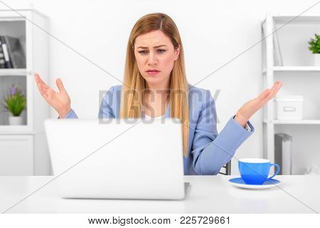 Attractive Woman Working At A Laptop In The Misunderstanding Of A Helpless Gesture. Difficulties At