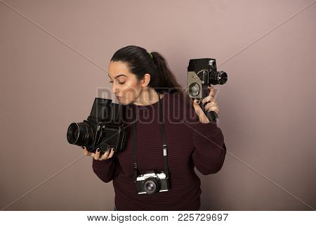 Young Woman Holding Two Vintage Cameras, One For Stills, One For Video, With A Small Compact Hanging