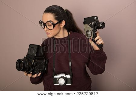 Nerdy Young Attractive Female Camera Boffin With Over Size Glasses In A Stereotypical Representation