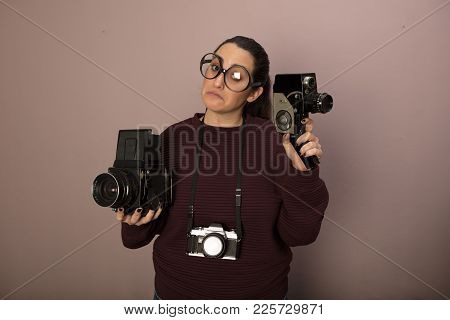 Nerdy Female Photography Buff Wearing Over Sized Glasses With Three Vintage Cameras Holding Up A Vid