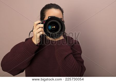 Female Photographer Focusing On The Viewer As You Look Directly Into A Professional Lens And Lens Ho