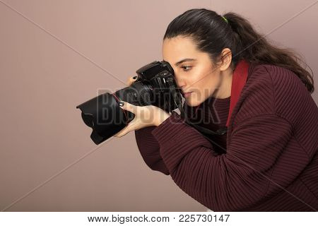 Young Woman Photographer Taking A Photo With A Professional Dslr And Lens Bending Forwards As She Fo