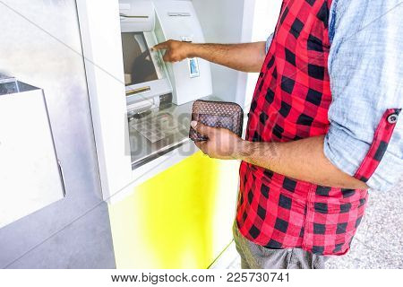 Man Withdrawing Money At Atm Machine Is Holding Wallet And Selecting Bank Service - Concept Of Every