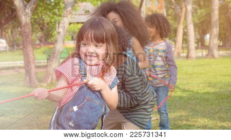Kid Girls And Boys Pulling A Long Red Rope, Playing Tug Of War In The Park That Look Like They Are V