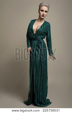 Fashion Studio Shot Of Beautiful Woman With Makeup And Hairstyle Wearing Evening Dress