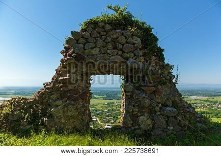 An Abandoned Fortress In The Mountains, Overgrown With Grass Against The Background Of Mountains And