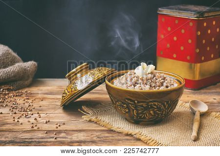 Hot Buckwheat Porridge With Butter In Ceramic Pot, On Wooden Table, Russian Cuisine, Simple Food.