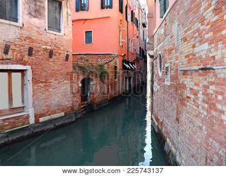 Very Narrow Canal With Old Houses With Low Tide In Venice Italy