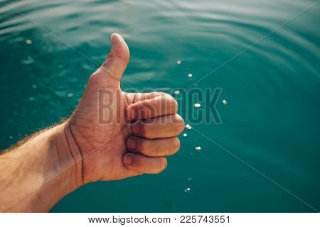 Male Giving Thumb Up By Outdoor Swimming Pool. Man Enjoying Refreshing Poolside Water In Summer Suns