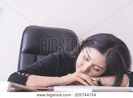 Tired Office Worker Is Taking A Nap On Office Desk