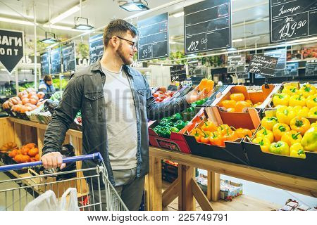 Man Seek Vegetables In Supermarket Stand Near Shelf With Salad Pepper