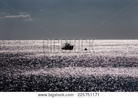 A Lonely Ship In The Sea Near A Buoy At Dusk. Open Sea And Skyline.