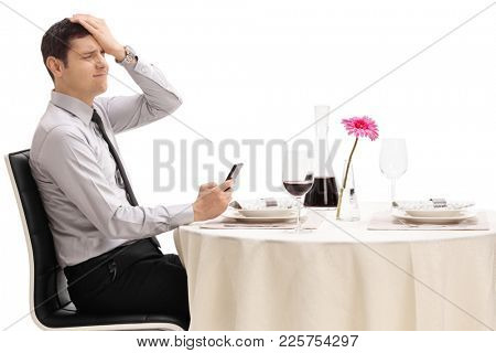 Disappointed man seated at a restaurant table reading a message on his phone isolated on white background
